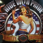 Ride with Pride on a Harley-Davidson poster and a young woman with brown shoulder length hair in white dressy top looking backwards over her shoulder